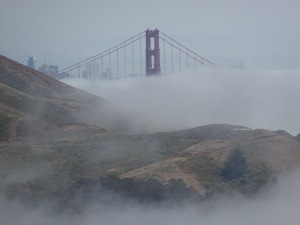 Fog-shrouded top of Golden Gate bridge, with Marin Headlands in foreground.